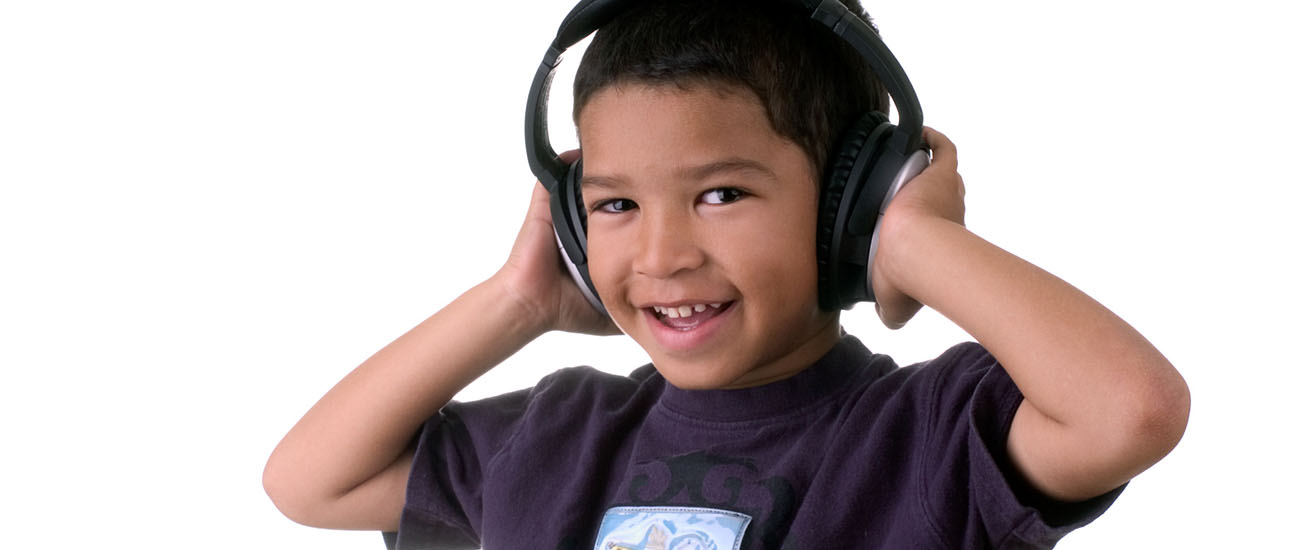Little boy wearing headphones, listening to music, smiling